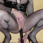 Tranny in PVC wearing a strapon